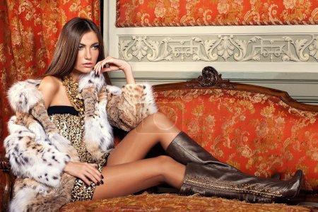 Model in fur coat on vintage sofa.