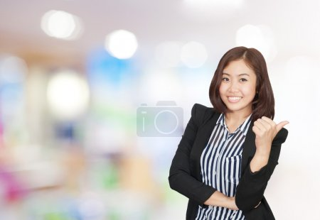 Businesswoman gesturing thumb up sign