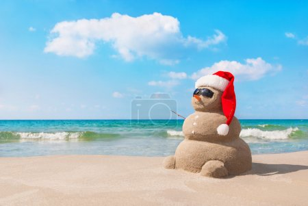 Photo for Sandy christmas snowman in red santa hat and sunglasses at sunny beach. Holiday concept for New Years Cards. - Royalty Free Image