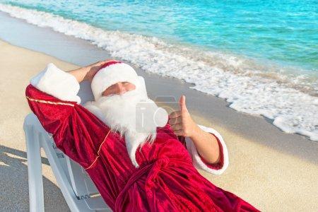 Santa Claus have e rest in chaise longue on sea beach