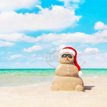 Sandy snowman at beach.