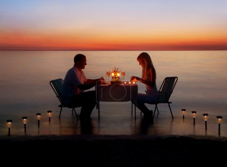 Photo for Loving couple share a romantic dinner with candles and lanterns light way at sea beach in water against wonderful sunset - Royalty Free Image