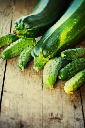 Zucchini and cucumbers on wooden table