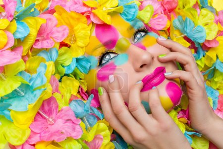 Photo for Closeup of young woman face in colorful flower petals. Beauty shot. Face paint. - Royalty Free Image