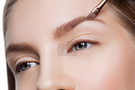 Photo for Beautician correcting eyebrows form on beautiful woman face. Beauty shot. Close-up. - Royalty Free Image