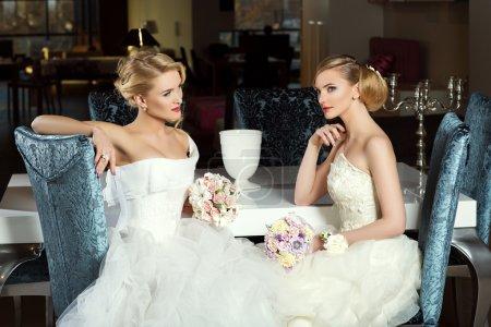 Photo pour Deux belles jeunes mariées en robes de mariée de mode assis près de la table. Plan intérieur . - image libre de droit