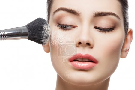 Beautiful girl applying loose powder with brush