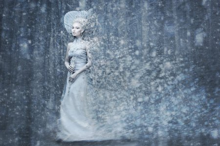 Beautiful young woman. Fairy tale snow queen in silver dress and crown with staff in magic forest. Copy space.