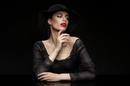 Photo for Beautiful young woman with red llips in black hat. Over dark background. Copy space. - Royalty Free Image