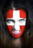 Portrait of a woman with the flag of the Switzerland  painted on her face