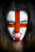 Portrait of a woman with the flag of the England  painted on her face