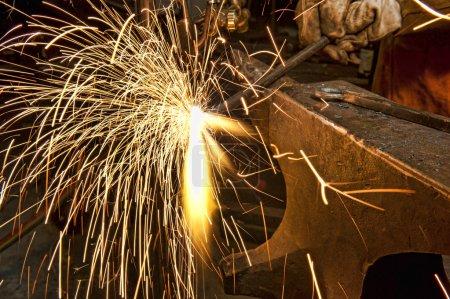 Photo pour Un fabricant de métal utilisant une torche pour chauffer un morceau de métal afin de le façonner - image libre de droit