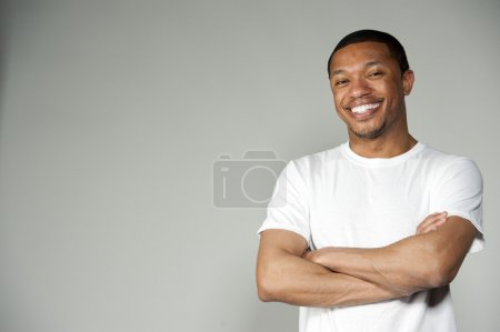 Photo for A happy attractive black male wearing a simple white t-shirt in a studio setting on a gray background acting funny - Royalty Free Image