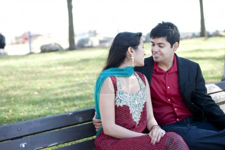 Photo for A young and happy Indian couple posing on a park bench in the Fall - Royalty Free Image