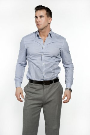 Photo for Athletic and attractive caucasian male wearing a fitted blue shirt and gray suit pants in a studio setting on a white background posing and looking to the left - Royalty Free Image