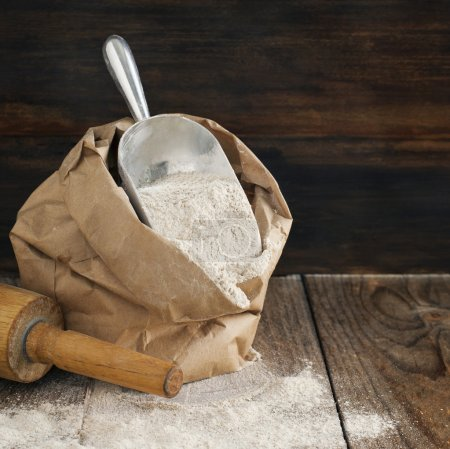 Rye flour in brown paper bag on wooden background.