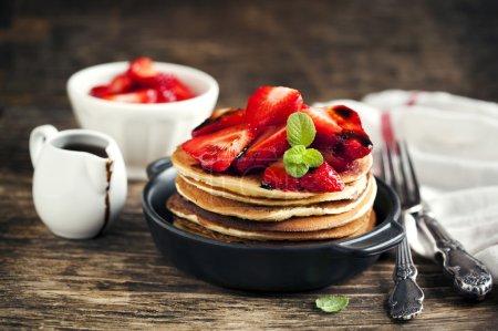 Stapel Pfannkuchen mit frischen Erdbeeren und Balsamico-Glas in der Pfanne