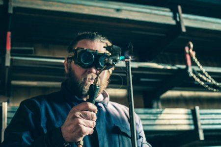 Photo for Beard Man with goggles soldering iron pipe - Royalty Free Image