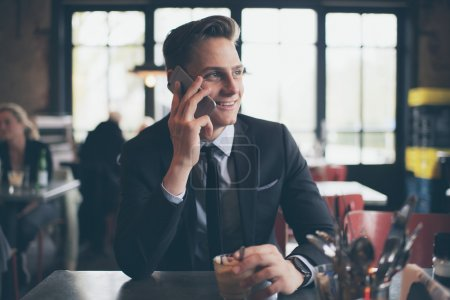 Smiling young businessman calling