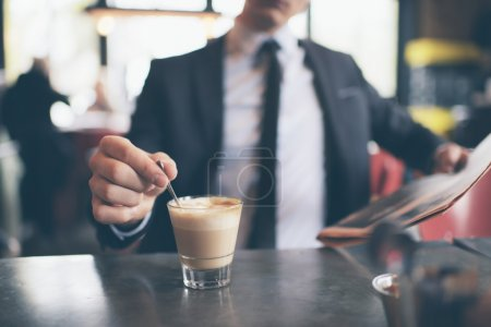 Hand of businessman stirring coffee