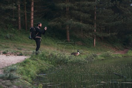 Hiker taking pictures of nature with smartphone