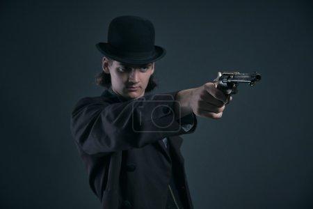 Photo pour Photographiez occidentale 1900 fashion homme, aux cheveux châtains et chapeau. Studio tiré contre gris. - image libre de droit