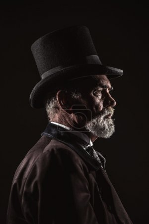 Photo for Vintage victorian man with black hat and gray hair and beard. Studio shot against dark background. - Royalty Free Image