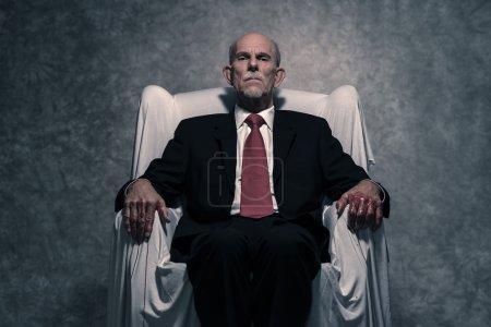 Un hombre de negocios corrupto con manos ensangrentadas sentado en una silla blanca. Gr.