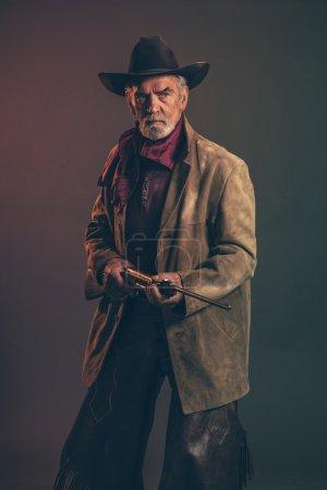 Photo pour Vieux baises cowboy western avec barbe grise et chapeau brun tenant fusil. Studio de clé faible tir. - image libre de droit