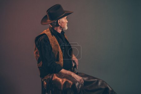 Old rough western cowboy with gray beard and brown hat. Low key