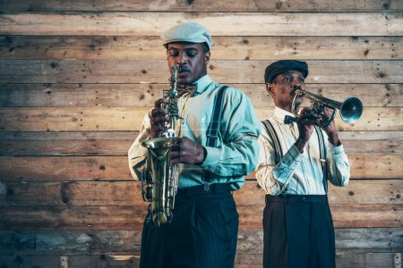 Photo for Two african american jazz musicians playing trumpet and saxophone. Standing in front of old wooden wall. - Royalty Free Image