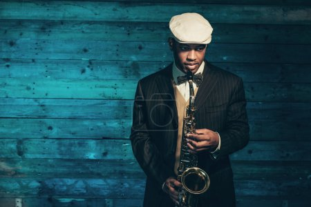Vintage african american jazz musician with saxophone in front o