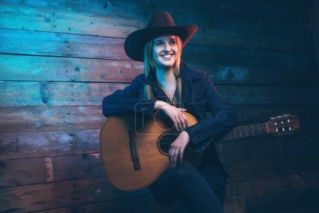 Photo pour Cowgirl chanteuse country avec guitare acoustique. Portant un jean bleu et un chapeau marron. Devant un mur en bois . - image libre de droit