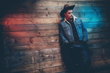 Photo pour Homme fashion de hiver cow-boy jeans. Porter le chapeau brun, veste de jeans et pantalons. Appuyé contre le mur en bois ancienne. - image libre de droit