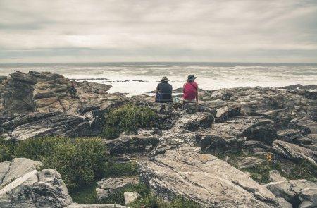 Couple assis sur rocher le long de la côte sauvage de Tsitsikamma Natio