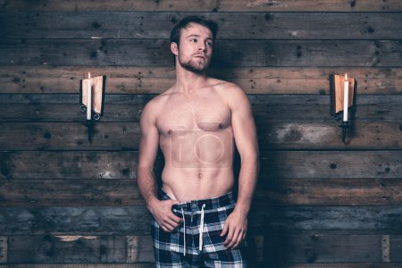 Man with blonde hair and bare chest wearing blue flannel pants.