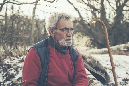 Photo pour Gros plan Vieil homme sérieux se reposant dans la forêt avec sa canne tout en regardant loin . - image libre de droit