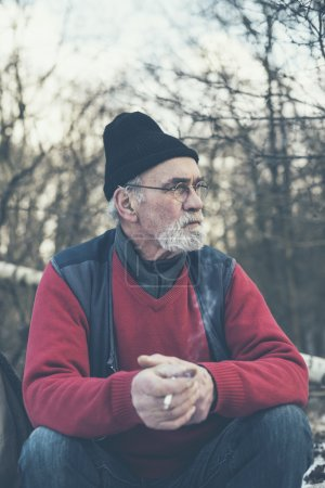 Photo pour Elderly man with a grey beard and glasses sitting smoking in a winter forest in warm winter clothing staring off thoughtfully to the side as he reminisces - image libre de droit