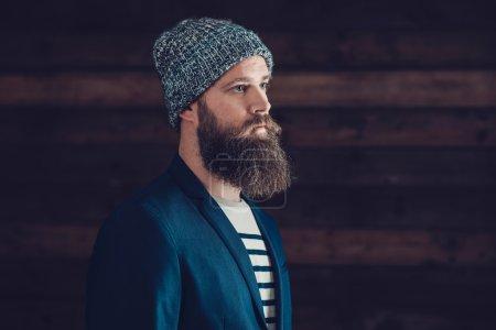 Photo pour Gros plan Vue latérale d'un bouc sérieux avec bonnet gris regardant vers la droite du cadre avec un fond mural en bois . - image libre de droit