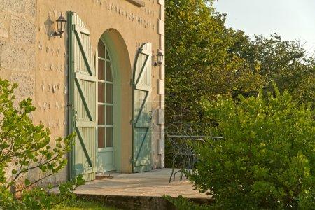 Photo pour Porte d'entrée cintrée à une maison avec volets dans un mur extérieur rustique texturé rugueux entouré de verdure au soleil du soir - image libre de droit