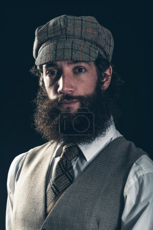 Photo for Attractive bearded man in vintage fashion wearing a cloth peaked cap and waistcoat looking at the camera with an enigmatic smile, dark background - Royalty Free Image