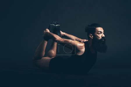 Photo for Athletic Guy with Long Beard and Mustache Doing Dhanurasana Bow Yoga Pose While Facing to the Right on a Black Background. - Royalty Free Image