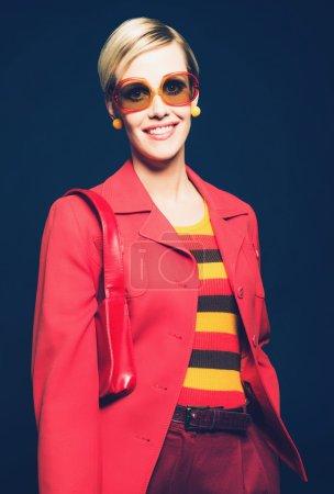 Photo pour Femme amicale de sourire dans la mode d'été à la mode utilisant une tenue et une veste rayées rouges et jaunes colorées élégantes avec des lunettes de soleil et sac à main modernes, portrait de studio - image libre de droit
