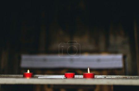 Foto de Tres velas votivas rojas encendidas en una iglesia ofrecidas en oración o en recuerdo en un concepto de religión y fe - Imagen libre de derechos