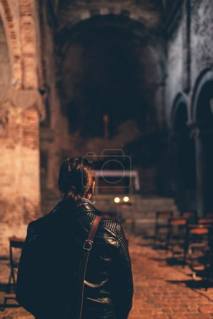Woman standing in the dark interior of a church