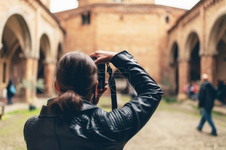 Female tourist photographing an ancient church