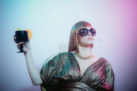Foto de Primer plano de mujer sofisticada y glamurosa con el pelo rojo usando gafas de sol fumar cigarrillo y sosteniendo copa de vino, mirando a la distancia con expresión aburrida - Imagen libre de derechos