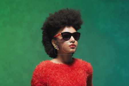 Photo for Close up Pretty Young Woman with Afro Hair, Looking into the Distance with Sunglasses Against Green Wall Background. - Royalty Free Image
