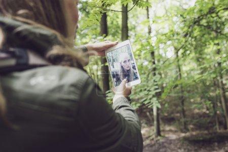 Woman in forest making selfie.