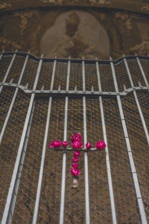 Photo pour Croix religieuse de roses roses sur clôture. - image libre de droit